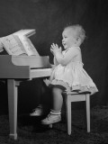 Girl Sitting at Piano Photographic Print