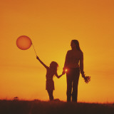 Mother and Daughter Walking at Sunset Holding Balloon Photographic Print by Dennis Hallinan
