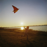 Boy Flying a Kite at Sunset Photographic Print by Dennis Hallinan