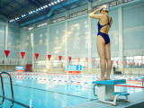 Young Female Swimmer Adjusting Swimming Cap Atop Starting Block Photographic Print