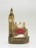 Close-Up of a Toy Bus in a Snow Globe in Front of a Figurine of a Clock Tower Photographic Print