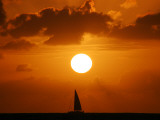 Sailboat on Ocean in Front of Setting Sun Photographic Print by Andrew Castellano