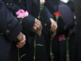 Mourners Hold Flowers Outside Photographie par Bulent Kilic