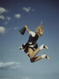 Cheerleader Jumping Holding Megaphone Photographic Print by Dennis Hallinan