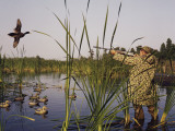 Hunter Aiming Rifle at Flying Duck Photographic Print by Dennis Hallinan