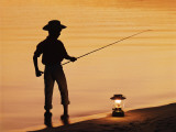 Boy Pole Fishing by Shoreline with an Oil Lamp Photographic Print by Dennis Hallinan