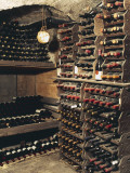 Wine Bottles on a Rack in a Wine Cellar Papier Photo par G. Cigolini