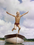 Boy Jumping Off Bow of Boat into Water Photographic Print by Dennis Hallinan