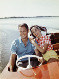 Smiling Retro Couple Enjoying a Speed Boat Ride Photographic Print by Dennis Hallinan