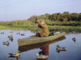 Hunter Sitting in Canoe Surrounded by Duck Decoys Photographic Print by Dennis Hallinan