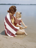 Retro Mother and Daughter Lying Down on Lakeshore Photographic Print by Dennis Hallinan