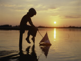Silhouette of Boy Sitting at Pier with Toy Sailboat Photographic Print by Dennis Hallinan