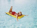 Happy Woman Sun on Bathing Inflatable Pool Raft Photographic Print by Dennis Hallinan