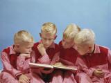 Boys Wearing Pajamas Reading a Book Photographic Print by Dennis Hallinan