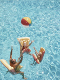 Family Tossing Beach Ball While Floating on Pool Rafts Photographic Print by Dennis Hallinan