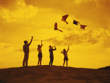 Friends flying kites on a hill at sunset Photographic Print by Dennis Hallinan