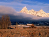 View of Historic Old Barn and Snow-Covered Teton Mountain Range Photographic Print by Jeff Foott
