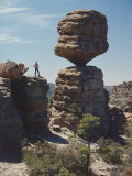 Man Stands on High Rock, Looks at Balancing Rock Formation Photographic Print by Jeff Foott