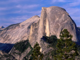 Pine Trees Grow on the Face of Glacier Point, Half Dome Looming in the Distance Photographic Print by Jeff Foott