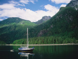 Detail of a Sailboat on Water Near Mountains Photographic Print by Jeff Foott