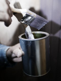 Close-Up of a Person's Hand Holding a Paintbrush and a Paint Can Photographic Print