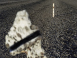 A Stone with a Black Stripe and a Pole Sticking Out of Gravel Photographic Print