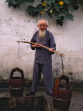 China, Anhui Province, Old Man Fetching Water with Buckets by the Well Photographic Print by Keren Su