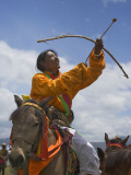 China, Western Sichuan Province, Litang, Tibetan Man Performing Archery on Horseback at Horse Race Photographic Print by Keren Su