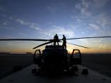 En UH-60 Black Hawk-helikopter på landingsplatformen ved solnedgang Fotografisk tryk