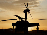 A UH-60L Black Hawk Helicopter Silhouetted by the Setting Sun Photographic Print