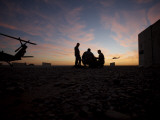 A UH-60 Black Hawk Crew Carry Out a Mission Brief at Sunset Photographic Print