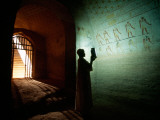 A Man Illuminates Hieroglyphics on a Wall in a Nubian King's Tomb Photographic Print by Randy Olson