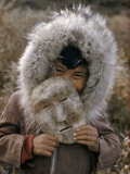 A Nunamiut Boy in a Fur-Trimmed Parka Holds a Mask of Caribou Hide Photographic Print by Thomas J. Abercrombie