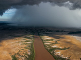 Monsoon Rains over a Muddy River Photographic Print by Randy Olson