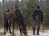 An Outfitter Lets His Horse Graze During a Snow Storm Photographic Print by Annie Griffiths
