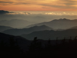 Sunset Casts a Colorful Glow over Mountaintops Shrouded in Fog Fotoprint van James P. Blair