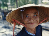 An Elderly Vietnamese Woman in a Native Hat Smiles as She Is Photographed Photographie par Steve Raymer