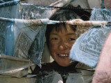 A Young Girl Looks Through Prayer Flags in the Sichuan Province Photographic Print by David Edwards