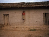A Tharu Girl Perches on a Support Post of a Traditional Longhouse Photographic Print by Maggie Steber