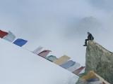 Mountain Climber Alex Lowe Sits on a Rock Near Tibetan Prayer Flags Photographic Print by Gordon Wiltsie