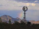 A Windmill on a Ranch with a Rainbow and Mountain Scenery Photographic Print by George Grall