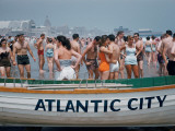 Throngs of Swimmers Stroll Behind a Wooden Lifeboat on the Beach Photographic Print by Volkmar K. Wentzel