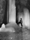 A Woman Standing Next to an Ice Pillar in a Cave Photographic Print by Norbert Casteret