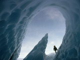 A Climber Stands Near the Opening of an Ice Cave Photographic Print by George F. Mobley
