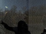 Shadow of a Woman Pointing to a Name on the The Vietnam Memorial Photographic Print by Todd Gipstein