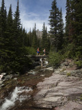 Two Hikers Cross a Small Stream in the Montana Backcountry Photographic Print by Michael Hanson