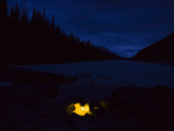 A Blurry Image of a Glowing Tent Near a Frozen Lake at Dark Photographic Print by Michael Hanson