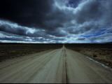 Dark Storm Clouds over Dirt Road and Grasslands of Saskatchewan Photographic Print by David Edwards