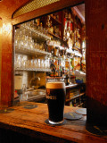 A Pint of Dark Beer Sits in a Pub Service Window Fotografiskt tryck av Jim Richardson
