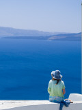 A Tourist Sits on a Stucco Wall Overlooking the Aegean Sea Photographic Print by Richard Nowitz